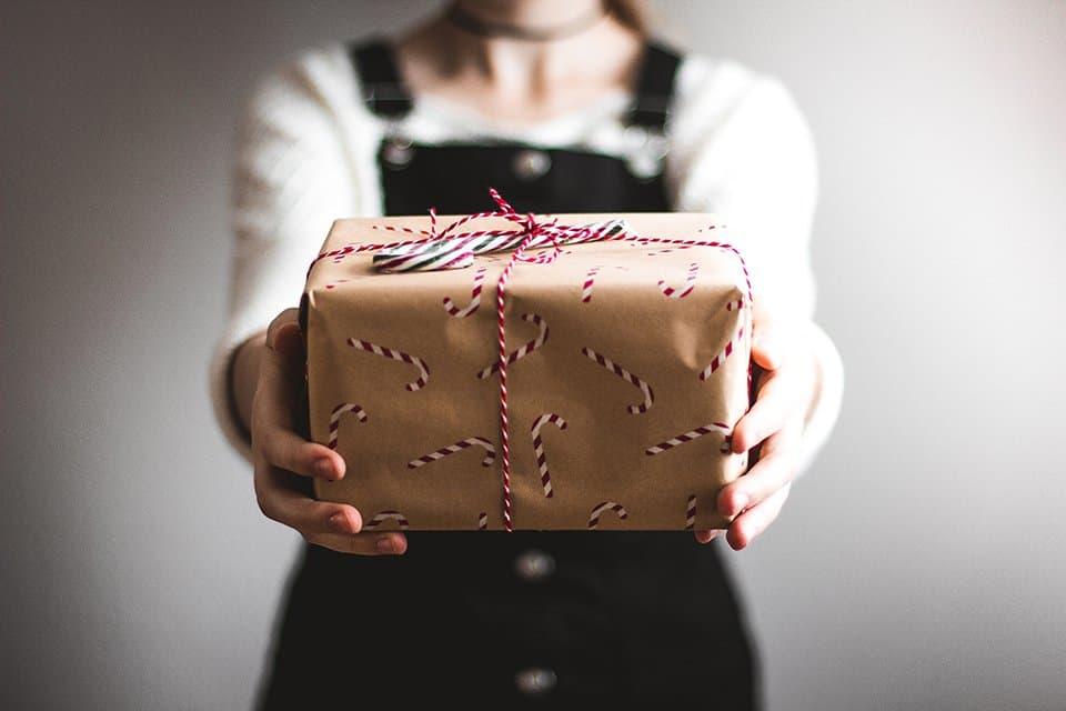 Imagen de una persona dando un regalo en el artículo sobre 7 ideas para regalos de última hora para Navidad