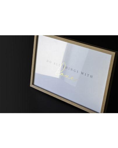 Lámina decorativa con mensaje oro With Love con marco de madera apoyada sobre una mesa